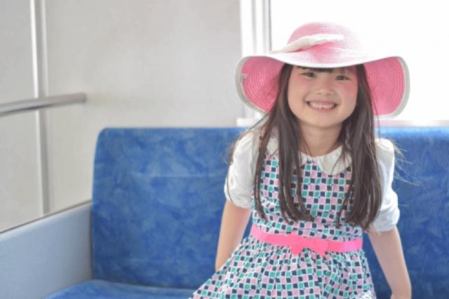電車に乗って笑う女児